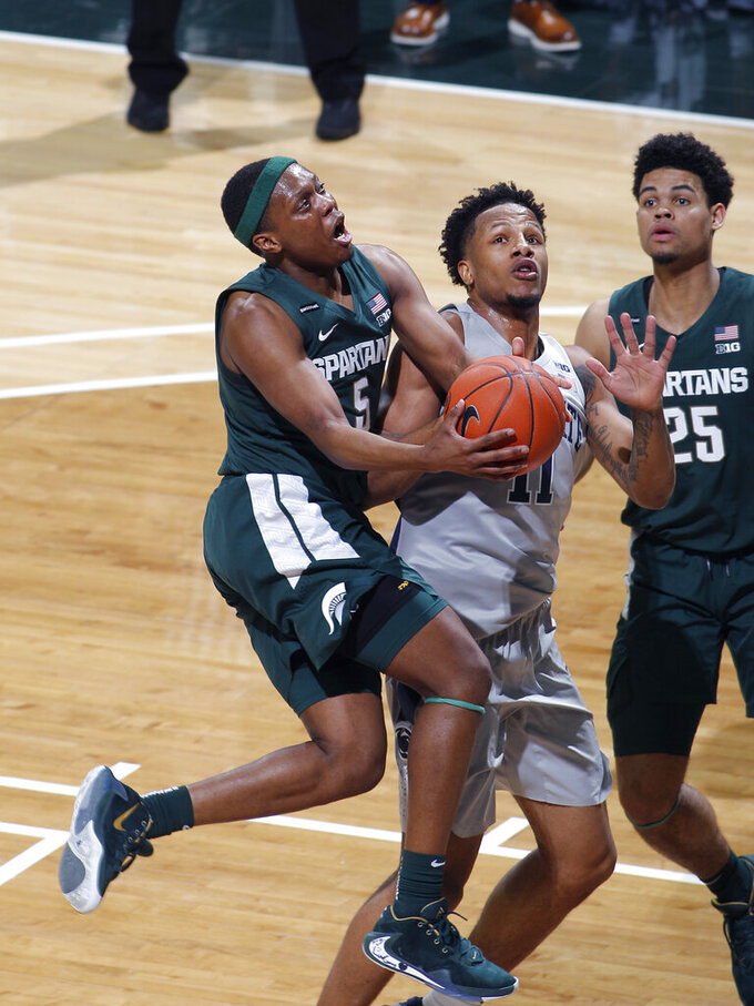 Michigan State's Cassius Winston, left, puts up a driving shot against Penn State's Lamar Stevens during the first half of an NCAA college basketball game Tuesday, Feb. 4, 2020, in East Lansing, Mich. (AP Photo/Al Goldis)