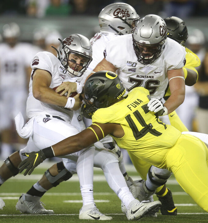 Montana quarterback Dalton Sneed, left, is sacked by Oregon's Mase Funa (No.47) off a block by Montana's Colton Keintz, right, during the first quarter of an NCAA college football game Saturday, Sept. 14, 2019, in Eugene, Ore. (AP Photo/Chris Pietsch)