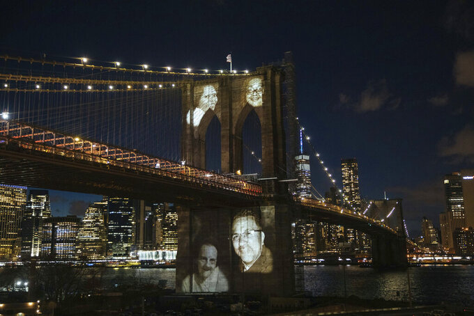 FILE - In this March 14, 2021 file photo images of New Yorkers who have died during the coronavirus pandemic are projected onto the Brooklyn Bridge during a commemoration ceremony in Brooklyn, NY. More than a year since the COVID-19 pandemic took hold in New York, Gov. Andrew Cuomo's administration's death toll is still nearly 11,000 lower than the federal government's own tally. (AP Photo/Kevin Hagen, File)