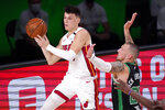 Miami Heat's Tyler Herro, left, passes the ball away from Boston Celtics' Daniel Theis (27) during the second half of an NBA conference final playoff basketball game Friday, Sept. 25, 2020, in Lake Buena Vista, Fla. (AP Photo/Mark J. Terrill)