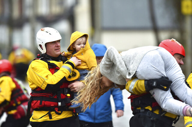 Rescue operations continue as emergency services take families to safety, after flooding in Nantgarw, Wales, Sunday, Feb. 16, 2020. Storm Dennis roared across Britain on Sunday, lashing towns and cities with high winds and dumping so much rain that authorities urged residents to protect themselves from