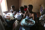 Mothers hold their babies delivered in a tiny apartment in the poor suburb of Mbare in Harare, Zimbabwe, Saturday, Nov. 16, 2019, with the help of 72-year old grandmother Esther Zinyoro Gwena. Grandmother Esther Zinyoro Gwena claims to be guided by the holy spirit and has become a local hero, as the country's economic crisis forces closure of medical facilities, and mothers-to-be seek out untrained birth attendants.(AP Photo/Tsvangirayi Mukwazhi)