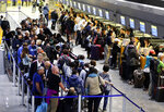 Passengers queue in a terminal at the airport in Frankfurt, Germany, Thursday, Nov. 7, 2019. The flight attendants' union Ufo is on strike at Lufthansa for 48 hours. (AP Photo/Michael Probst)