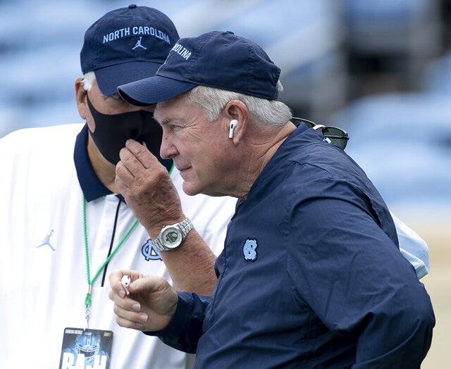 FILE - In this Saturday, Sept. 12, 2020, file photo, North Carolina head coach Mack Brown confers with assistant coach Ken Browning before an NCAA college football game against Syracuse, in Chapel Hill, N.C. It took Mack Brown less than two years to guide North Carolina's rise from two-win program to its highest ranking in more than two decades. The challenge now for the fifth-ranked Tar Heels is maintaining that status, which won't be easy for a program that hasn't shown much staying power in more than two decades since last cracking the top 5 during Brown's first stint in Chapel Hill. (Robert Willett/The News & Observer via AP, Pool, File)