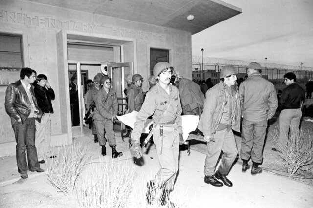 FILE - In this Feb. 3, 1980 file photo National Guardsmen carry the body of a prison inmate from the main entrance to the New Mexico State Penitentiary in Santa Fe, New Mexico. Forty years after inmates seized control of the New Mexico State Penitentiary, the costs related to the uprising are still being tallied. (AP Photo/Brian Horton,File)