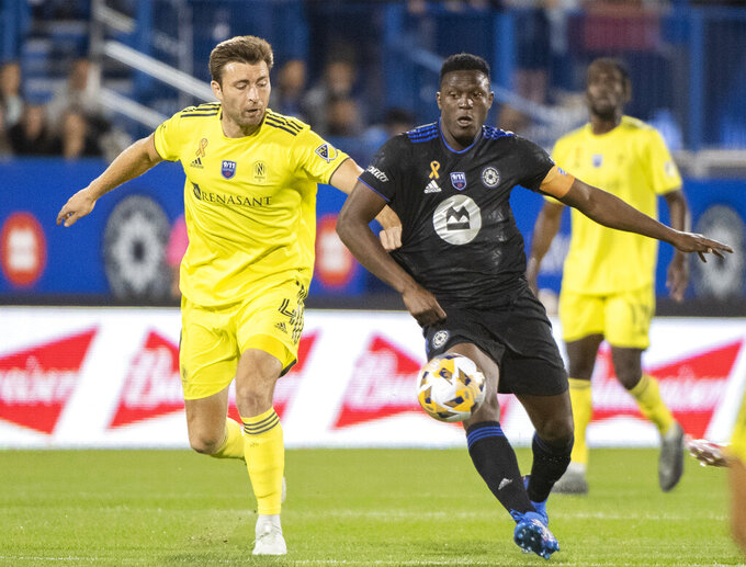 CF Montreal's Victor Wanyama, right, challenges Nashville SC's Dave Romney (4) during the first half of an MLS soccer match Saturday, Sept. 11, 2021, in Montreal. (Graham Hughes/The Canadian Press via AP)
