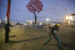Anti-government protesters pull down one of two metal tree sculptures that are emblematic of the government of Nicaraguan President Daniel Ortega, at the Jean Paul Jennie round-about in Managua, Nicaragua, Saturday, April 21, 2018. Ortega said Saturday that his government is willing to enter into talks over social security reforms that have sparked four days of protests and clashes in which, rights monitors say, at least 25 people have died. A journalist covering the unrest was also killed.  (AP Photo/Alfredo Zuniga)