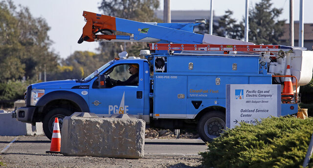 FILE - In this Feb. 11, 2020, file photo a Pacific Gas & Electric truck leaves the company's Oakland Service Center in Oakland, Calif. Pacific Gas and Electric said Tuesday, Feb. 18, that it expects to become more profitable than ever after it emerges from bankruptcy and pays off more than $25 billion in losses sustained in catastrophic wildfires ignited by its outdated equipment. (AP Photo/Ben Margot, File)