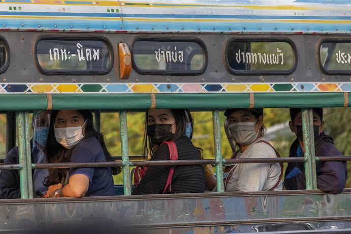 Migrant workers watch as other migrant workers and their families are carried in trucks to a field hospital for COVID-19 patents in Samut Sakhon, South of Bangkok, Thailand, Monday, Jan. 4, 2021. For much of 2020, Thailand had the coronavirus under control. After a strict nationwide lockdown in April and May, the number of new local infections dropped to zero, where they remained for the next six months. However, a new outbreak discovered in mid-December threatens to put Thailand back where it was in the toughest days of early 2020 (AP Photo/Gemunu Amarasinghe)