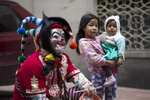 """Girls watch a performance by the Brazilian theater group Clowns of Shakespeare in Bogota, Colombia, Saturday, Oct. 26, 2019. The troupe's play titled """"Abrazo,"""" or Hug, is among the growing list of shows, plays, conferences and other artistic projects that have been abruptly canceled in Brazil since the nation's President Jair Bolsonaro took office Jan. 1, after the troupe talked politics with the audience during the show's debut. (AP Photo/Ivan Valencia)"""