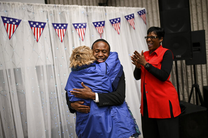 "Brooklyn Center Mayor Mike Elliott embraces Sue Low, of Maple Grove, after Elliot's inauguration ceremony, Wednesday, Jan. 2, 2019 at the Brooklyn Center Community Center, in Brooklyn Center, Minn. ""He's just an amazing guy and we're really excited for Brooklyn Center,"" said Low, who's known Elliott since he was in high school and has worked alongside him on various committees over the years. Elliott, who emigrated from Liberia as a child, is finding just how difficult it is to turn the page on the nation's racial history as he handles the fallout from a police shooting. (Aaron Lavinsky/Star Tribune via AP)"