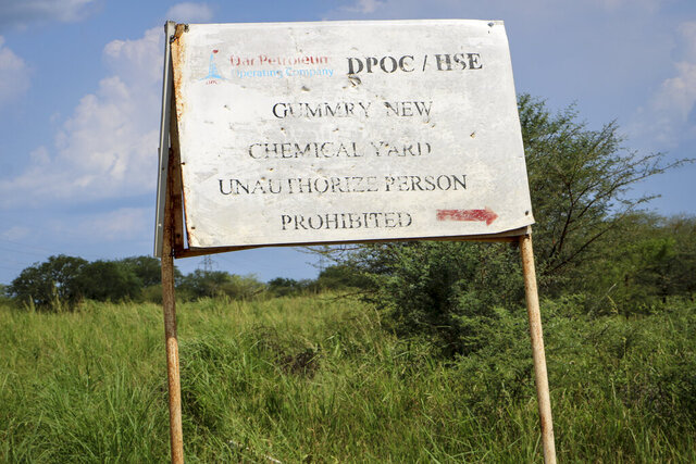 In this photo taken Monday, Oct. 1, 2018, a sign marks the chemical junkyard run by the Chinese-led Dar Petroleum Operating Company in Gumry, near Paloch, in South Sudan. The oil industry in South Sudan has left a landscape pocked with hundreds of open waste pits with the water and soil contaminated with toxic chemicals and heavy metals, and accounts of