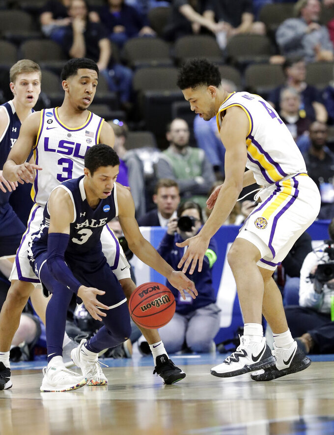 Yale guard Alex Copeland, center, loses control of the ball as he gets between LSU's Tremont Waters, left, and Skylar Mays during the first half of a first round men's college basketball game in the NCAA Tournament, in Jacksonville, Fla. Thursday, March 21, 2019. (AP Photo/John Raoux)