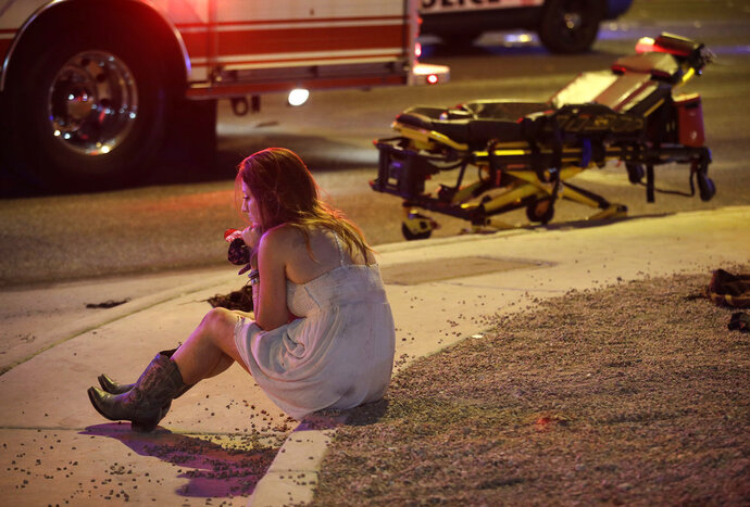 FILE - In this Oct. 2, 2017 file photo a woman sits on a curb at the scene of a shooting outside a music festival on the Las Vegas Strip. Police in Las Vegas plan to release witness statements and officer reports of the Oct. 1 gunfire that killed 58 people and injured hundreds in the deadliest mass shooting in modern U.S. history. The scheduled release of documents on Wednesday, May 16, 2018, comes more than seven months after the shooting on the Las Vegas Strip. (AP Photo/John Locher,File)