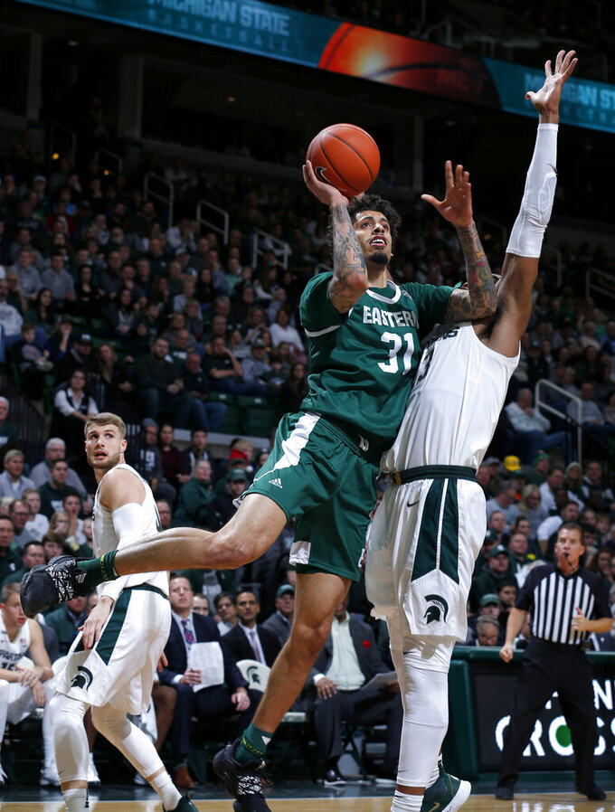 Eastern Michigan's Ty Groce, front left, goes to the basket against Michigan State's Xavier Tillman during the first half of an NCAA college basketball game, Saturday, Dec. 21, 2019, in East Lansing, Mich. (AP Photo/Al Goldis)