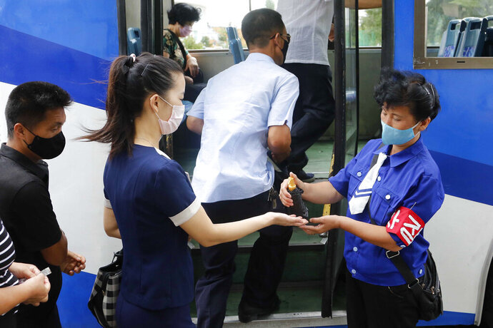 A passenger wearing a face mask to help curb the spread of the coronavirus is disinfected her hand before getting on a trolley bus in Pyongyang, North Korea, Thursday, Aug. 13, 2020. (AP Photo/Jon Chol Jin)