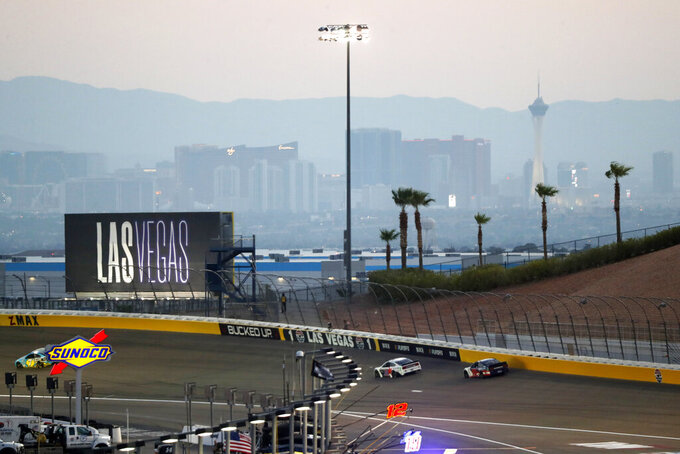 Las Vegas Strip casinos can be seen in the background as drivers race in a NASCAR Cup Series auto race at the Las Vegas Motor Speedway Sunday, Sept. 26, 2021, in Las Vegas. (AP Photo/Steve Marcus)