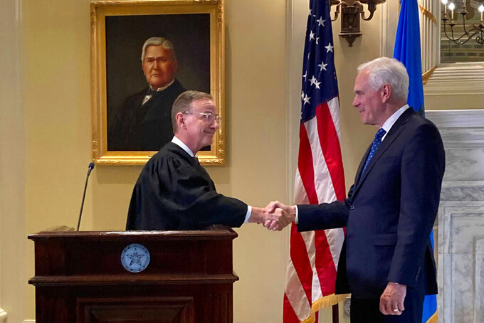 Oklahoma Supreme Court Justice John Kane, left, shakes hands with Oklahoma's new Attorney General John O'Connor after he swore O'Connor into office at the state Capitol, Friday, July 23, 2021, in Oklahoma City. (AP Photo/Sean Murphy)