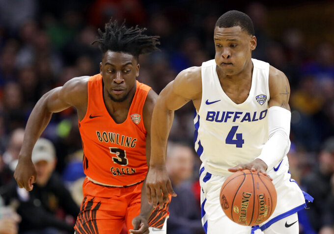 Buffalo's Davonta Jordan (4) drives against Bowling Green's Caleb Fields (3) during the first half of an NCAA college basketball championship game of the Mid-American Conference men's tournament, Saturday, March 16, 2019, in Cleveland. (AP Photo/Tony Dejak)