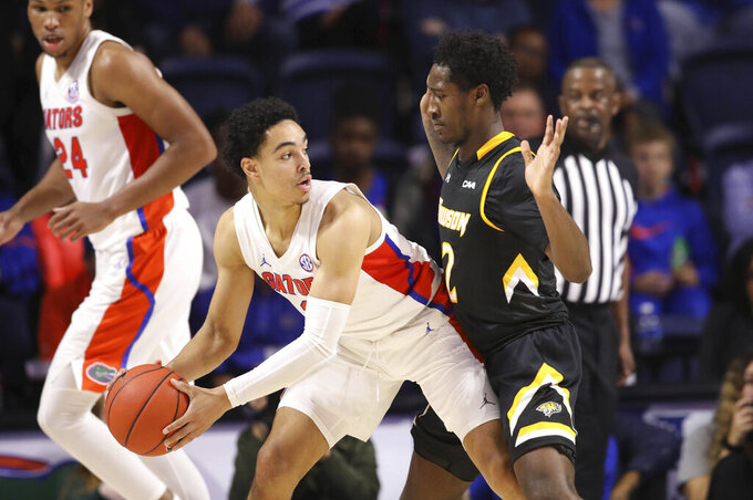 Towson guard Allen Betrand (2) defends Florida guard Andrew Nembhard (2) during the first half of an NCAA college basketball game Thursday, Nov. 14, 2019, in Gainesville, Fla. (AP Photo/Matt Stamey)