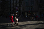 People wearing a face mask walk on Las Ramblas in Barcelona, Spain, Monday, July 27, 2020. Britain has put Spain back on its unsafe list and announced Saturday that travelers arriving in the U.K. from Spain must now quarantine for 14 days. (AP Photo/Felipe Dana)
