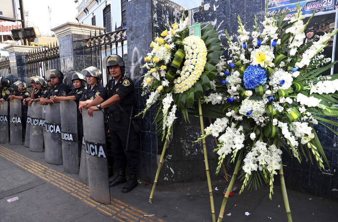 Flowers stand outside the party headquarters of Peru's late President Alan Garcia soon before his wake takes place in Lima, Peru, Wednesday, April 17, 2019. Garcia shot himself in the head and died Wednesday as officers waited to arrest him in a massive graft probe that has put the country's most prominent politicians behind bars and provoked a reckoning over corruption. (AP Photo/Martin Mejia)