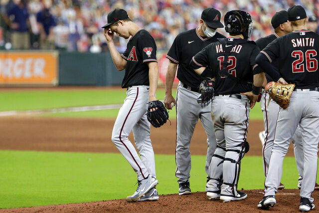 Arizona Diamondbacks starting pitcher Luke Weaver, left, scratches his head as he leaves the mound after being relieved after the Houston Astros scored two runs, during the sixth inning of a baseball game Saturday, Sept. 19, 2020, in Houston. (AP Photo/Michael Wyke)