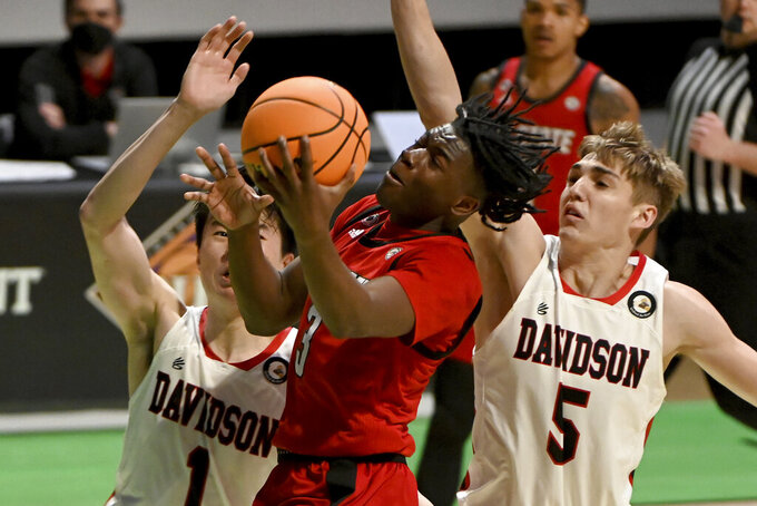 North Carolina State guard Cam Hayes (3) drives to the basket between Davidson forward Hyunjung Lee (1) and guard Grant Huffman (5) in the second half of an NCAA college basketball game in the first round of the NIT, Thursday, March 18, 2021, in Denton, Texas. North Carolina State won 75-61. (AP Photo/Matt Strasen)