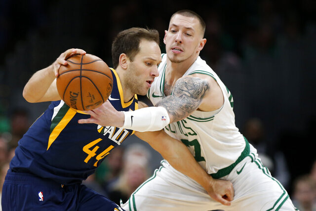 Boston Celtics' Daniel Theis, right, tries to knock the ball away from Utah Jazz's Bojan Bogdanovic during the fourth quarter of an NBA basketball game Friday, March 6, 2020, in Boston. (AP Photo/Winslow Townson)