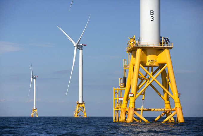 FILE - In this Aug. 15, 2016, file photo, three of Deepwater Wind's turbines stand in the water off Block Island, R.I. Massachusetts is poised to its next step in battling climate change. A landmark law signed by Mass. Gov. Charlie Baker in March 2021 has officially taken effect. A key goal of the new law is creating a net-zero greenhouse gas emission limit by 2050. The law also requires the creation of an additional 2,400 megawatts of offshore wind. (AP Photo/Michael Dwyer, File)