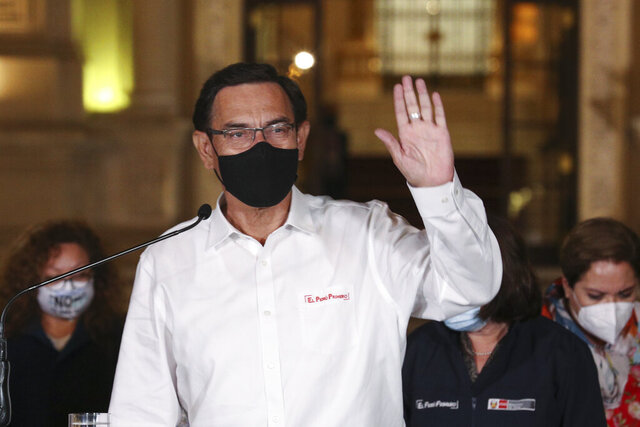 Peru's President Martin Vizcarra waves to reporters during a press conference at the presidential palace in Lima, Peru, after lawmakers voted his impeachment on Monday, Nov. 9, 2020, (AP Photo/Martin Mejia)