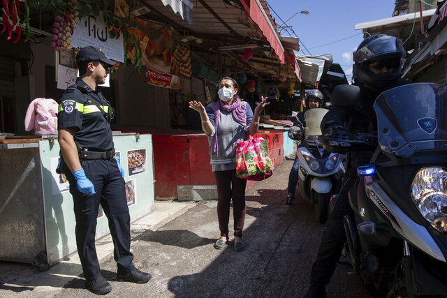 A woman argues with a police officer as police shut down a food market in order to reduce the spread of the coronavirus, in Tel Aviv, Israel, Sunday, March 22, 2020. (AP Photo/Oded Balilty)