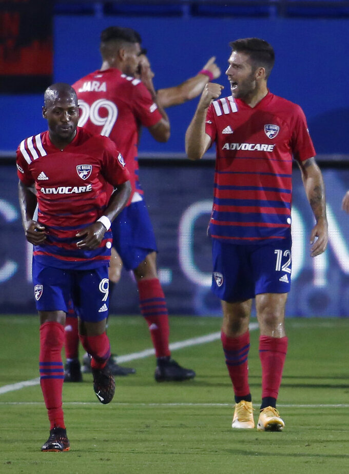 FC Dallas' Ryan Hollingshead, (12) pumps his fist as he reacts to fans as teammate Fafa Picault (9) runs back to set up on defense following Hollingshead's goal during the first half of an MLS soccer game against Sporting KC  in Frisco, Texas, Wednesday, Oct. 14, 2020. (Steve Hamm/The Dallas Morning News via AP)