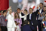 Incumbent President Andrzej Duda, right, his wife Agata Kornhauser-Duda, left, and daughter Kinga, wave to supporters in Pultusk, Poland, Sunday, July 12, 2020. An exit poll in Poland's presidential runoff election shows a tight race that is too close to call between the conservative incumbent, Andrzej Duda, and the liberal Warsaw mayor, Rafal Trzaskowski.(AP Photo/Czarek Sokolowski)