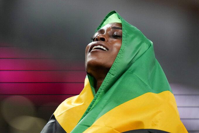 Elaine Thompson-Herah, of Jamaica, celebrates after winning the women's 100-meter final at the 2020 Summer Olympics, Saturday, July 31, 2021, in Tokyo. (AP Photo/Petr David Josek)