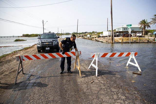 A Corpus Christi police office places a barricade to close Laguna Shores Boulevard due to flooding on Sunday, Sept. 20, 2020, in Corpus Christi, Texas. Forecasters say Tropical Storm Beta is slowly churning through the Gulf of Mexico toward Texas and Louisiana, stirring worries that it could bring heavy rain, flooding and storm surge to a storm-weary stretch of the Gulf Coast. (Courtney Sacco/Corpus Christi Caller-Times via AP)