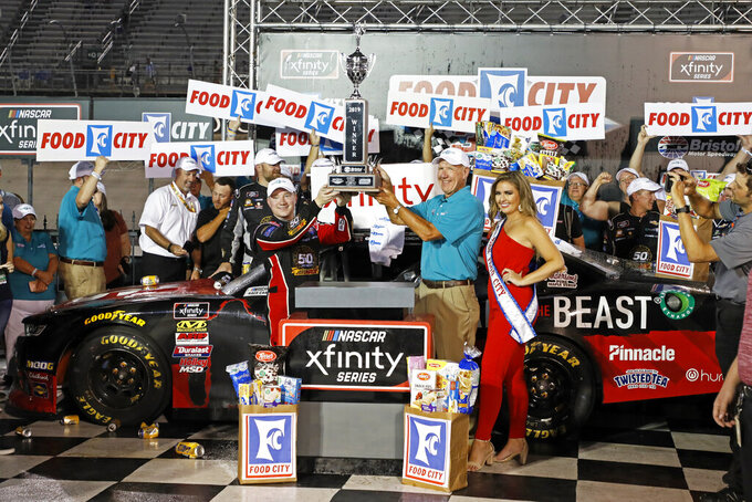 Driver Tyler Reddick hoists the trophy with Steve Smith, president and CEO of Food City after winning the NASCAR Xfinity Series auto race on Friday, Aug. 16, 2019, in Bristol, Tenn. (AP Photo/Wade Payne)