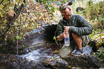 Peter Weinberger, 33, refills his water bottle in a creek along Camas Creek Road in Glacier National Park, Mont., on Sept. 23, 2020. Weinberger was near the end of his walk on the Continental Divide Trail, a route that leads from the Mexican border to the Canadian border. (Hunter D'Antuono/Flathead Beacon via AP)