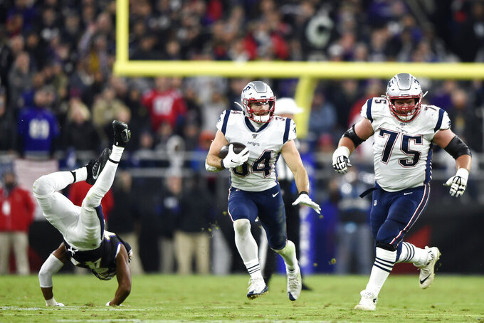 Baltimore Ravens cornerback Marlon Humphrey, left, falls forward as New England Patriots running back Rex Burkhead (34) runs with the ball behind blocking from center Ted Karras (75) during the first half of an NFL football game, Sunday, Nov. 3, 2019, in Baltimore. (AP Photo/Gail Burton)