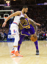 Philadelphia 76ers' Ben Simmons, left, of Australia, tries to reach around Los Angeles Lakers' LeBron James, right, for the ball during the first half of an NBA basketball game, Sunday, Feb. 10, 2019, in Philadelphia. (AP Photo/Chris Szagola)