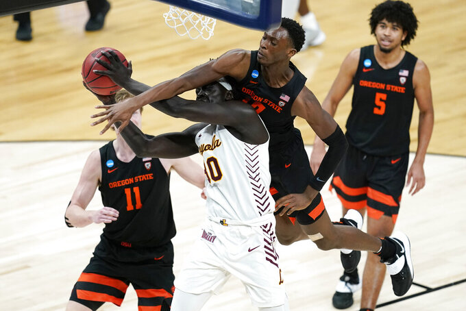 Loyola Chicago forward Aher Uguak (30) is fouled by Oregon State forward Warith Alatishe, right, while driving to the basket during the second half of a Sweet 16 game in the NCAA men's college basketball tournament at Bankers Life Fieldhouse, Saturday, March 27, 2021, in Indianapolis. (AP Photo/Darron Cummings)