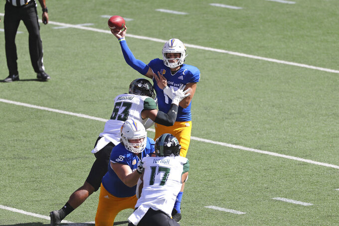 As Hawaii linebacker Darius Muasau (53) charges him, San Jose State quarterback Nick Starkel (17) makes a pass in the first half of an NCAA college football game Saturday, Dec. 5, 2020, in Honolulu. (AP Photo/Marco Garcia)