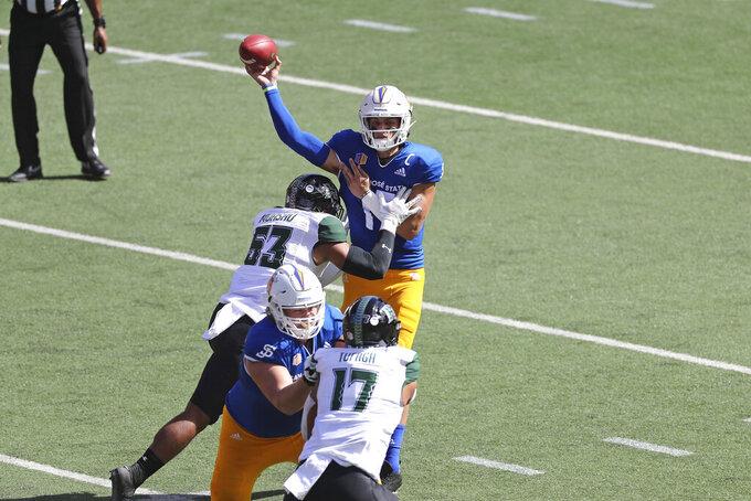 As Hawaii linebacker Darius Muasau (53) charges him, San Jose State quarterback Nick Starkel (17) makes a pass in the first half of an NCAA college football game Saturday, Dec. 5, 2020, in Honolulu. (AP Photo/Marco Garcia)