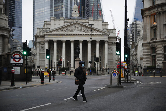 A man crosses the street backdropped by the Royal Exchange in the City of London financial district in London, Jan. 5, 2021, on the first morning of England entering a third national lockdown since the coronavirus outbreak began. British Prime Minister Boris Johnson on Monday night announced a tough new stay-at-home order that will last at least six weeks, as authorities struggle to stem a surge in COVID-19 infections that threatens to overwhelm hospitals around the U.K. (AP Photo/Matt Dunham)