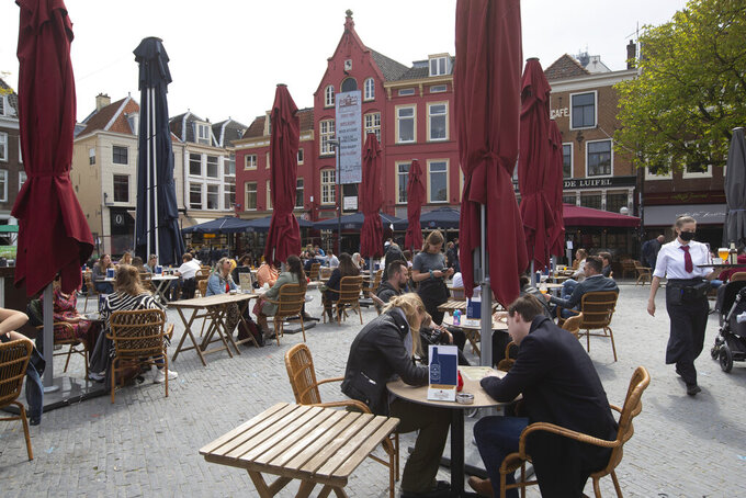 Dutch customers eager for their first drink of coffee or something stronger at a cafe terrace have flocked to outdoor seating as the Netherlands' lockdown eased in Utrecht, Wednesday, April 28, 2021. The Netherlands became the latest European country to begin cautiously relaxing its lockdown even as infection rates and intensive care occupancy remain stubbornly high. The Dutch follow Italy, Greece, France and other European nations in moving to reopen society and edge away from economically crippling lockdowns in the coming weeks.(AP Photo/Peter Dejong)