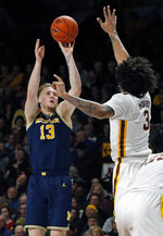 Michigan's Ignas Brazdeikis, left, shoots over Minnesota's Jordan Murphy in the second half of an NCAA college basketball game Thursday, Feb. 21, 2019, in Minneapolis. (AP Photo/Jim Mone)