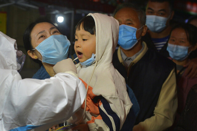 A medical staff takes a swab from a child as residents wearing face masks to help curb the spread of the coronavirus line up for the COVID-19 test near the residential area in Qingdao in east China's Shandong province on Monday, Oct. 12, 2020. Authorities in the eastern Chinese port city of Qingdao said Tuesday that they have completed coronavirus tests on more than 3 million people following the country's first reported local outbreak of the virus in nearly two months. (Chinatopix via AP)