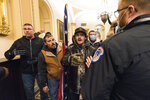 FILE - In this Wednesday, Jan. 6, 2021, file photo, Kevin Seefried, second from left, holds a Confederate battle flag as he and other insurrectionists loyal to President Donald Trump are confronted by U.S. Capitol Police officers outside the Senate Chamber inside the Capitol in Washington.  War-like imagery began to take hold in Republican circles after the attack on the U.S. Capitol by a mob of Trump's supporters, with some elected officials and party leaders rejecting pleas to tone down rhetoric calling for a second civil war.(AP Photo/Manuel Balce Ceneta)