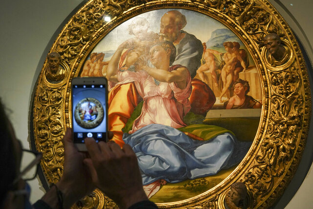 A member of the media takes a picture of 15th century painting