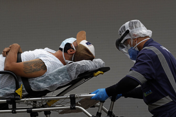A healthcare worker transfers a patient suspected of having COVID-19 from an ambulance into the HRAN public hospital in Brasilia, Brazil, Thursday, April 29, 2021. (AP Photo/Eraldo Peres)